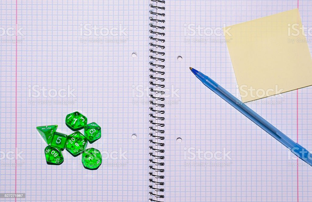 open exercise book with card, pen and role playing dices stock photo