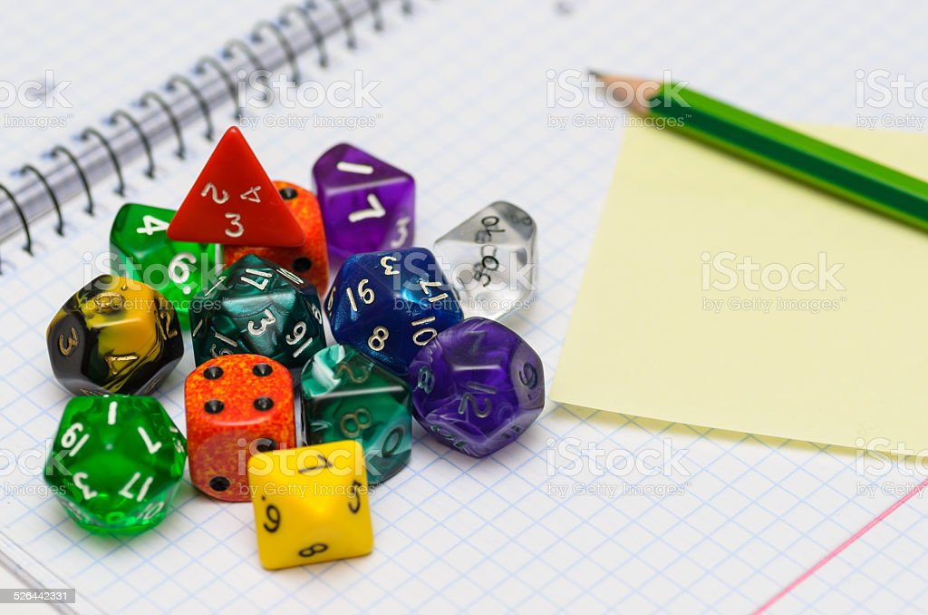 open exercise book with set of rpg dices stock photo