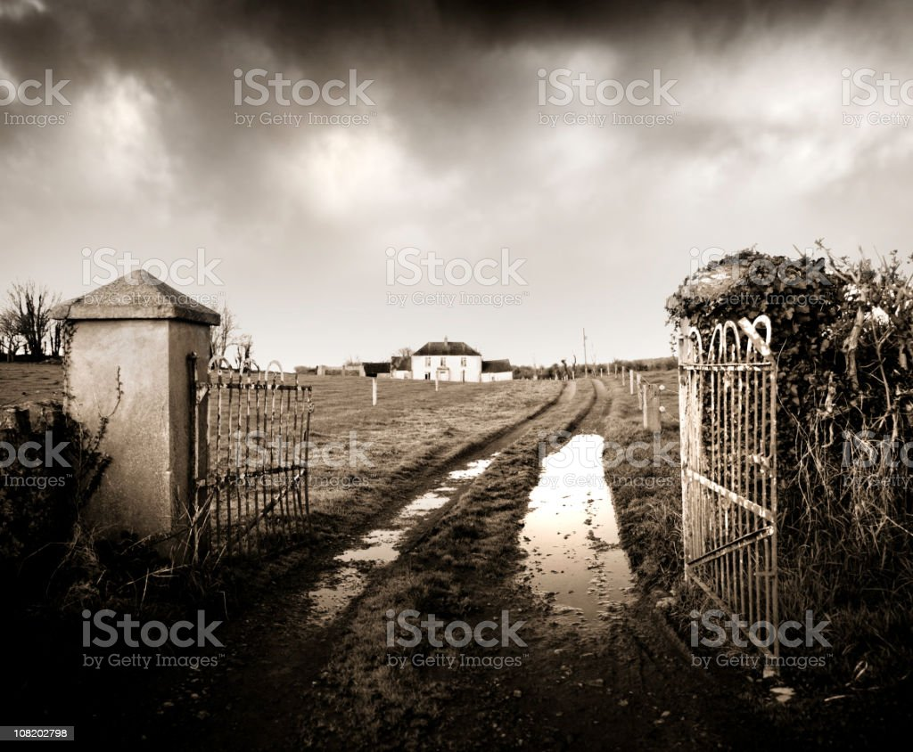 Open Gates to Derelict Farmhouse with Muddy Tire Tracks royalty-free stock photo