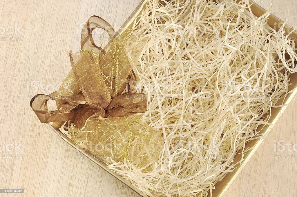 Open gift box and bow - filled with packing bast stock photo