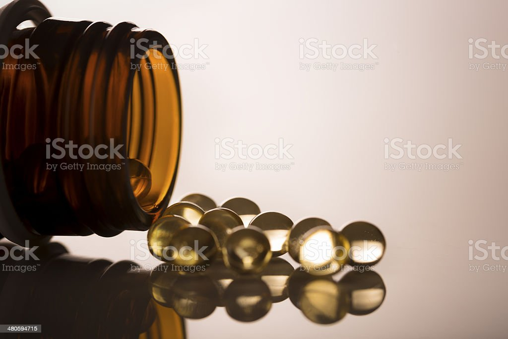 Open glass jar with Gel capsules Vitamin D royalty-free stock photo
