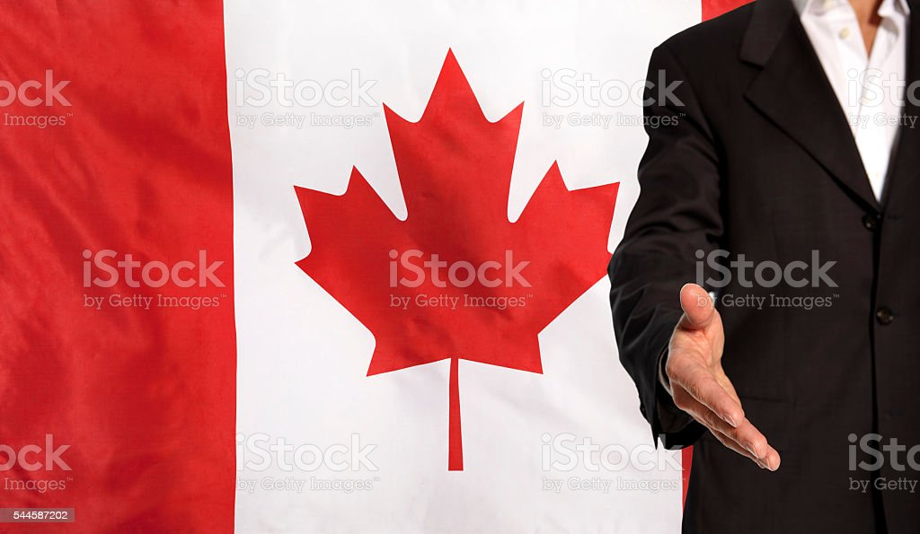 Open hand and Canada flag in the background stock photo