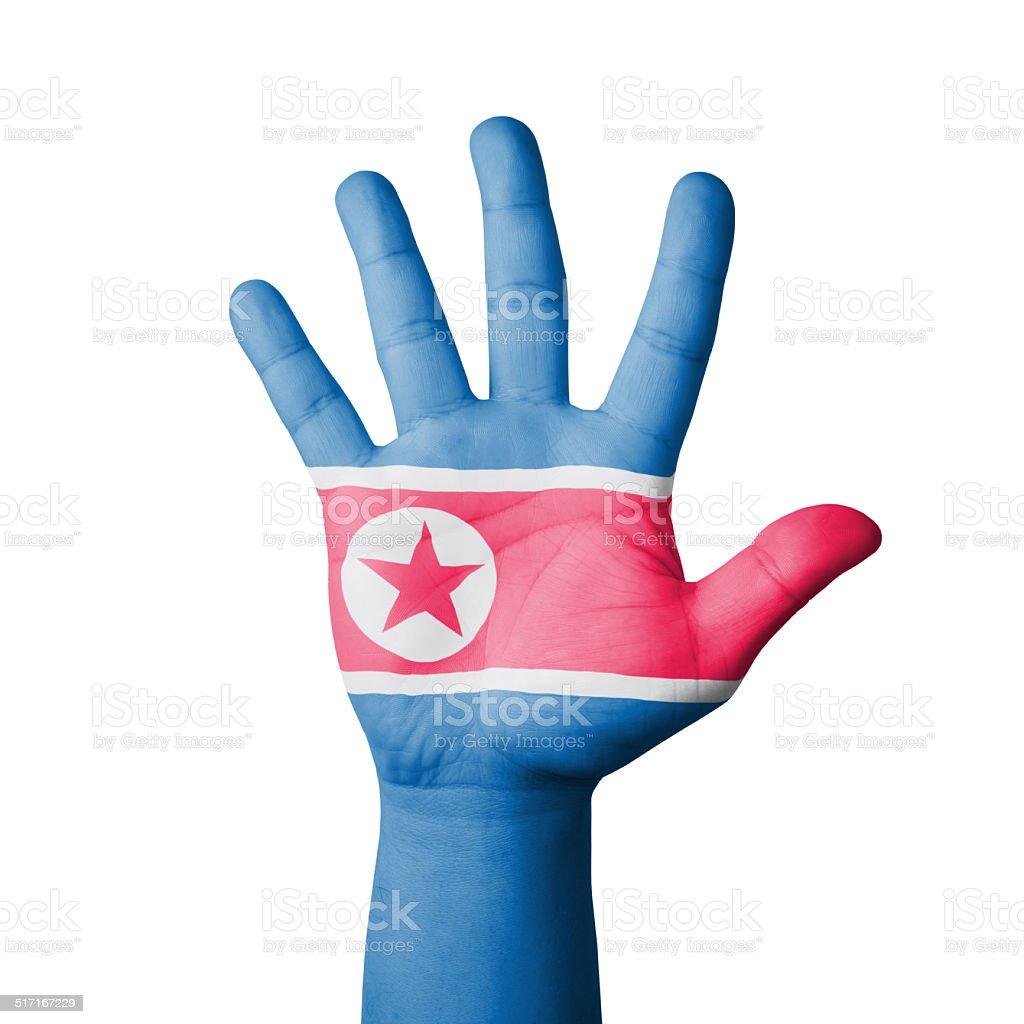 Open hand raised, North Korea flag painted stock photo