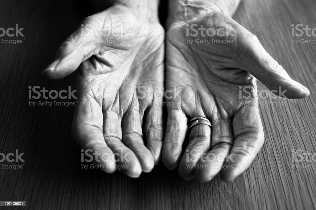 Open hands of an older person resting on a wooden surface royalty-free stock photo