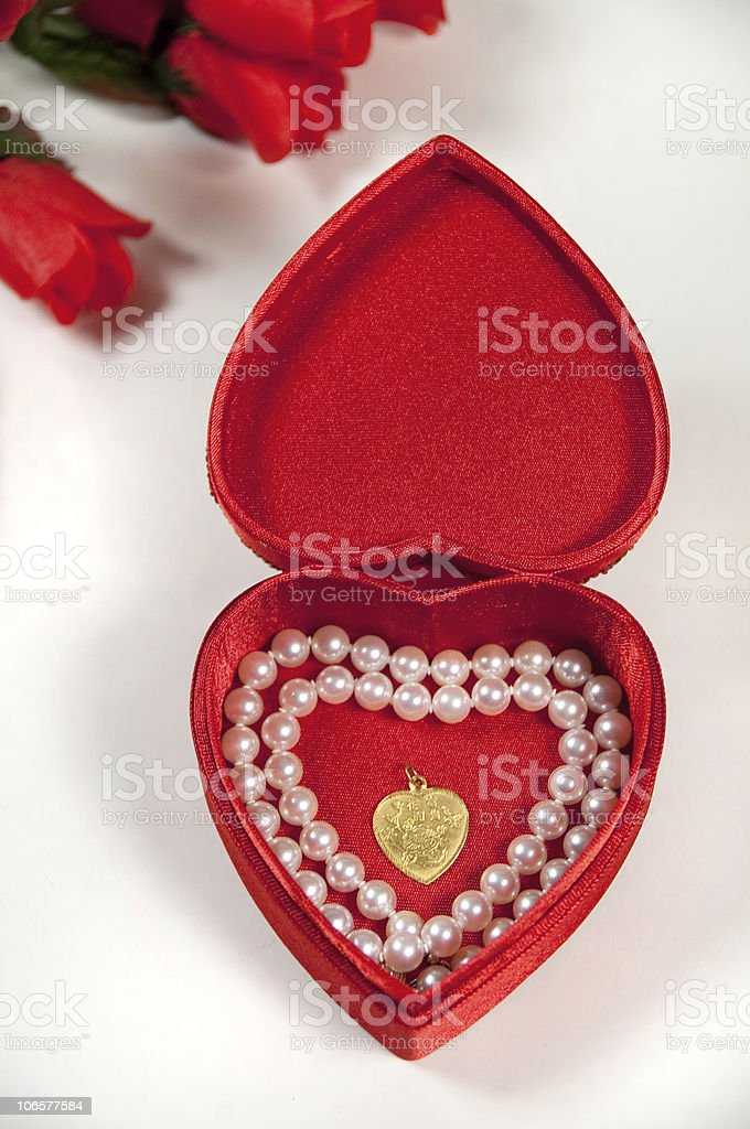 open heart shaped box with pearls and necklace stock photo
