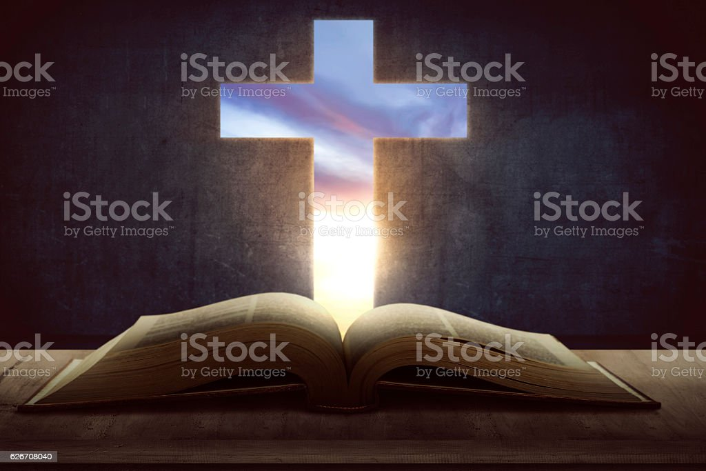 Open holy bible with wooden cross in the middle stock photo