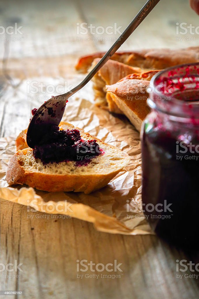 Open jar and slice of bread with chokeberry jam stock photo