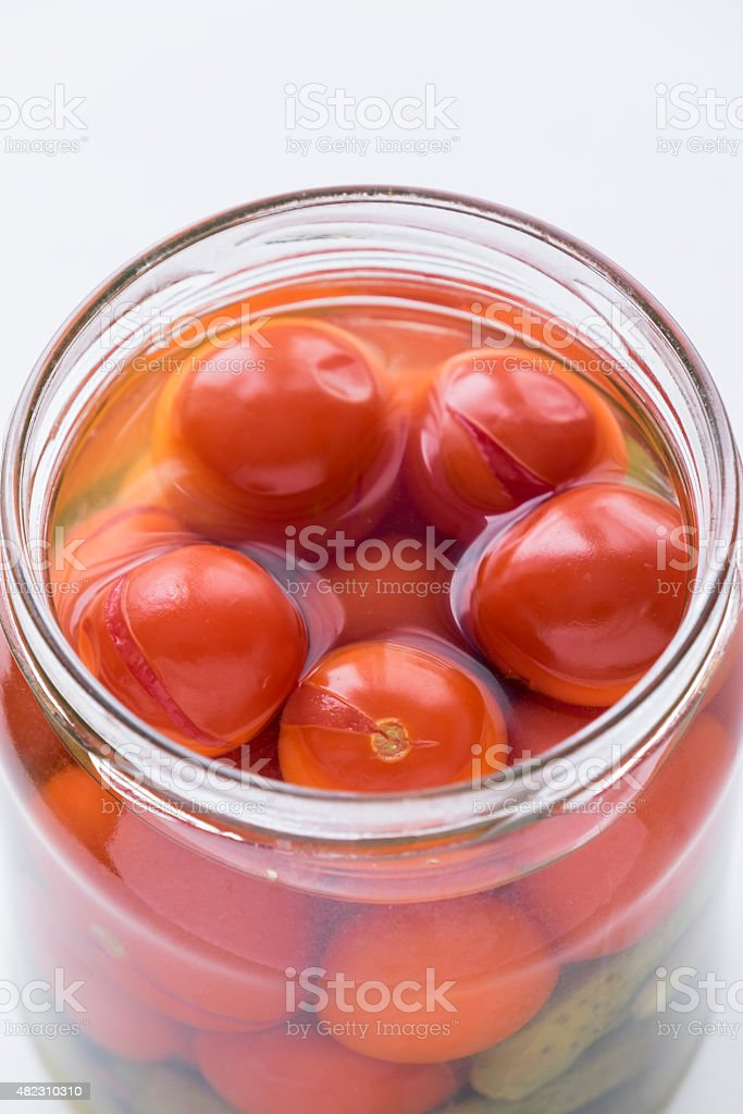 Open jar with pickled cherry tomatoes stock photo