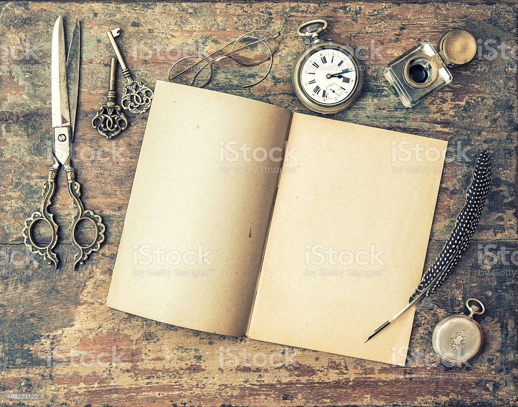 Open journal book and vintage writing tools on wooden table stock photo