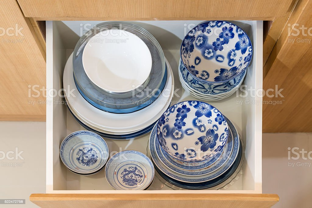 Open kitchen drawer with bowls and plates stock photo
