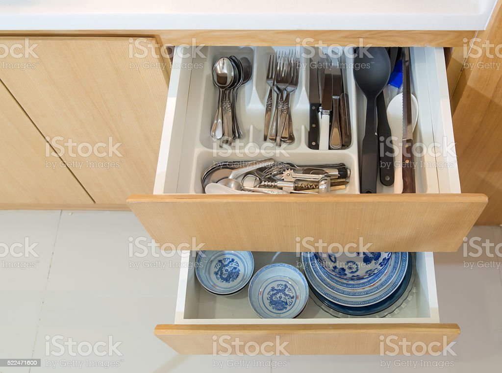 Open kitchen drawer with silverware and plate stock photo