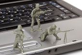 Open laptop computer with toy soldiers