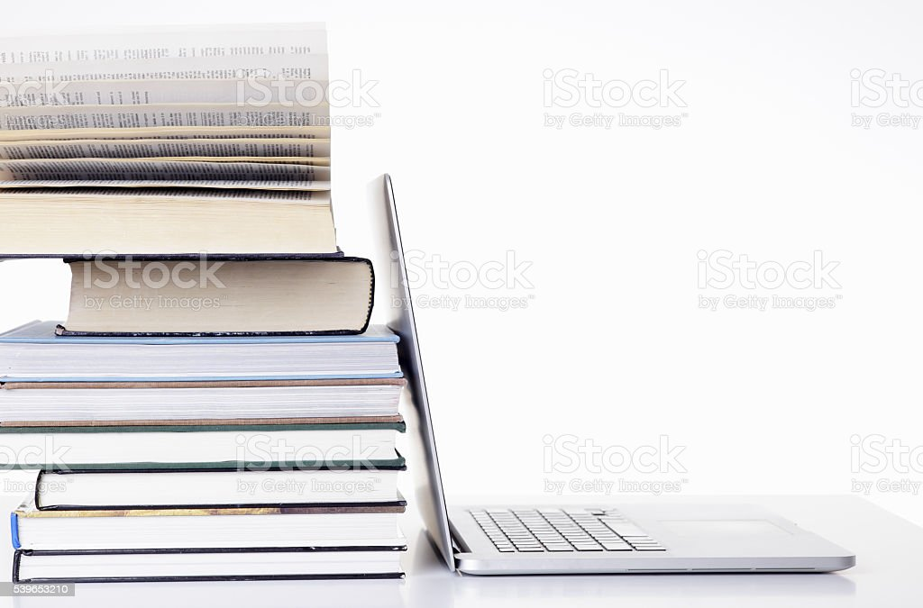 Open laptop screen leaning against a stack of books stock photo