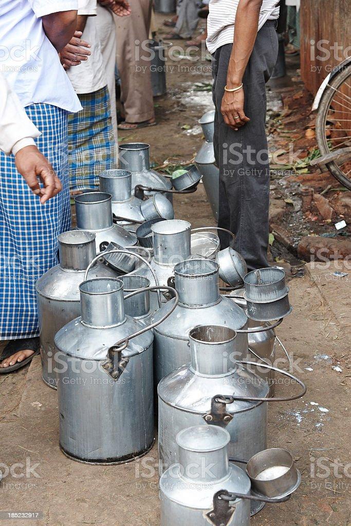 Open milk churns lined up on Varanasi pavement stock photo