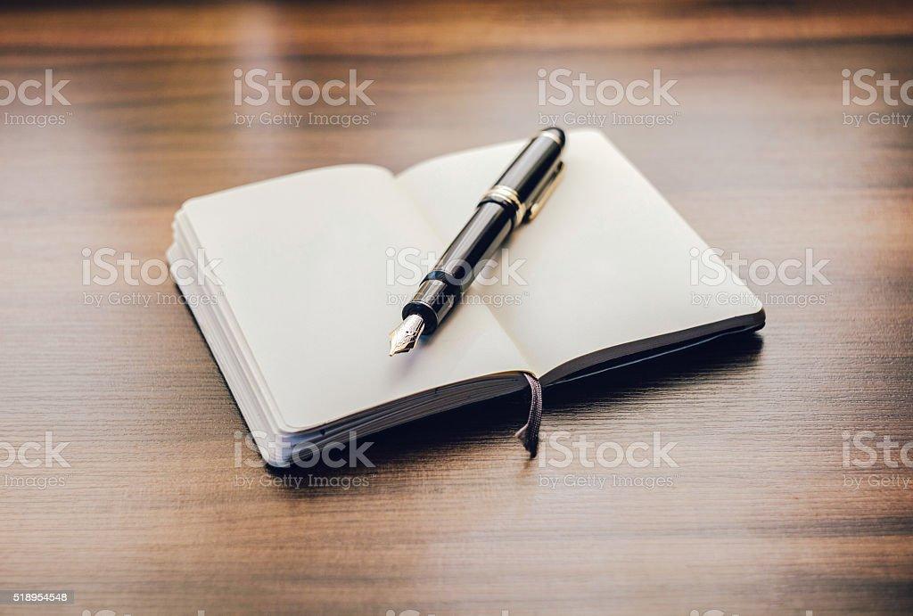 Open moleskin book with fountain pen on wood stock photo