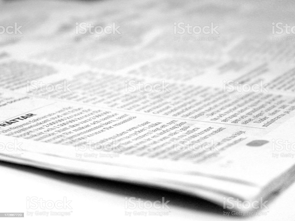 Open newspaper focused on a small corner of printed text stock photo