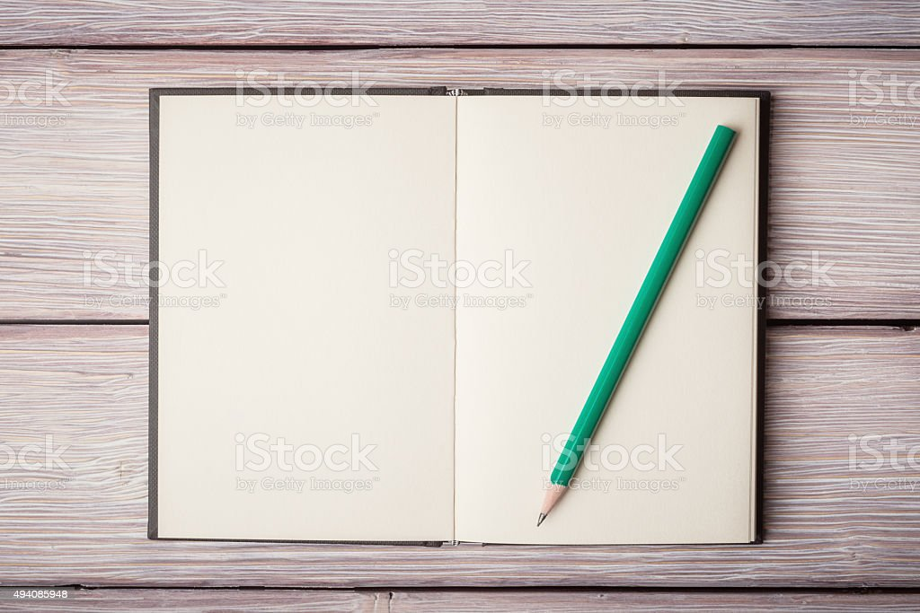 Open notebook and a pancil on old wooden desk stock photo