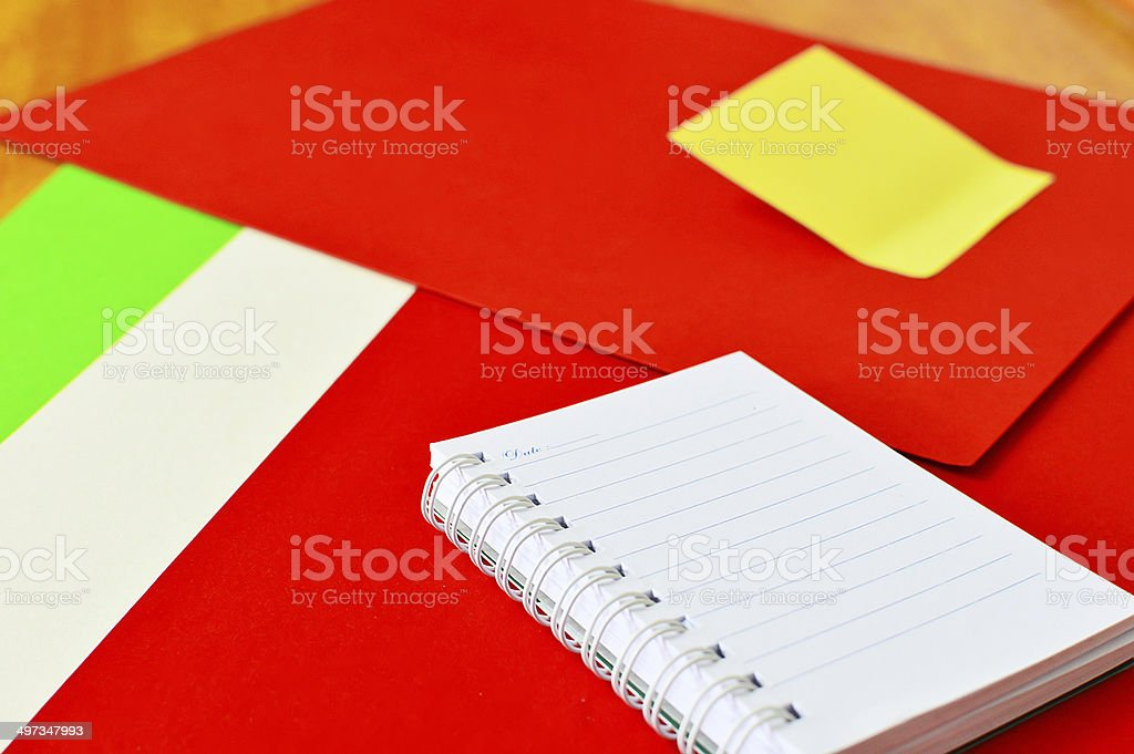 Open notebook and yellow post it isolated on red background stock photo