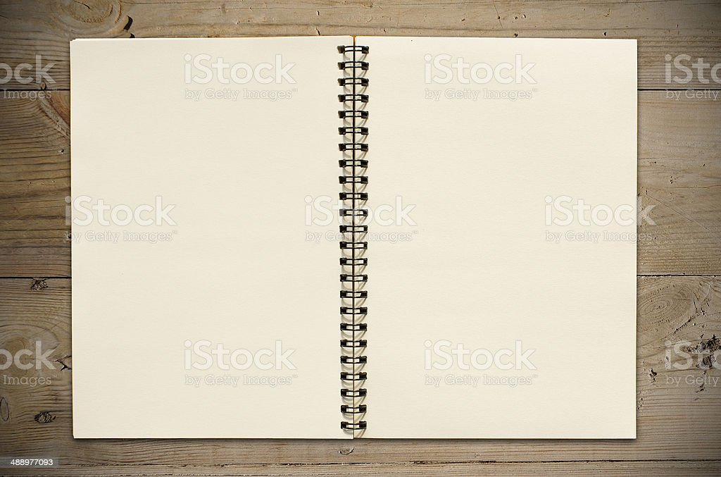 Open notebook on wooden table stock photo
