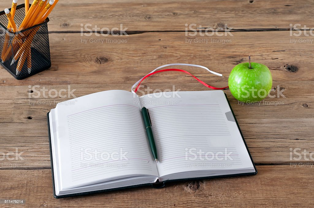 Open notebook with blank pages, pen and green apple stock photo