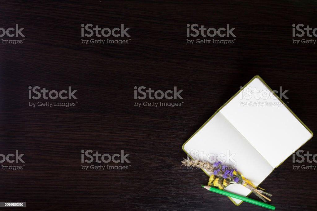 Open notebook with boutonniere and green pencil in the corner of dark wooden background. stock photo