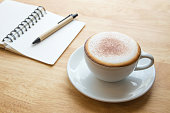 Open notebook with coffee cup.