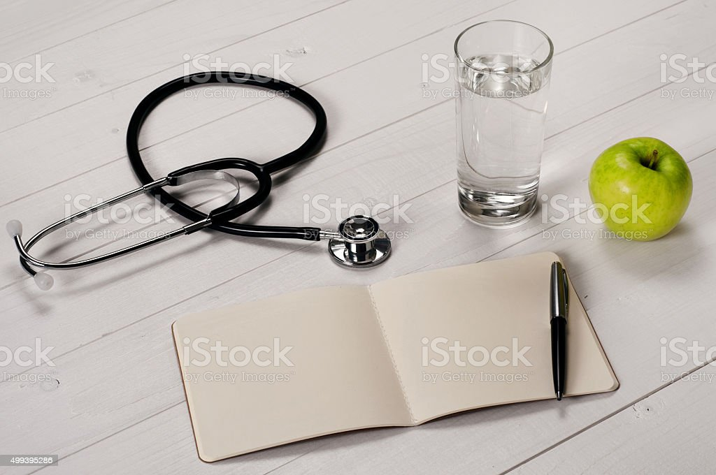Open notebook with pen, stethoscope, apple and a glass water stock photo