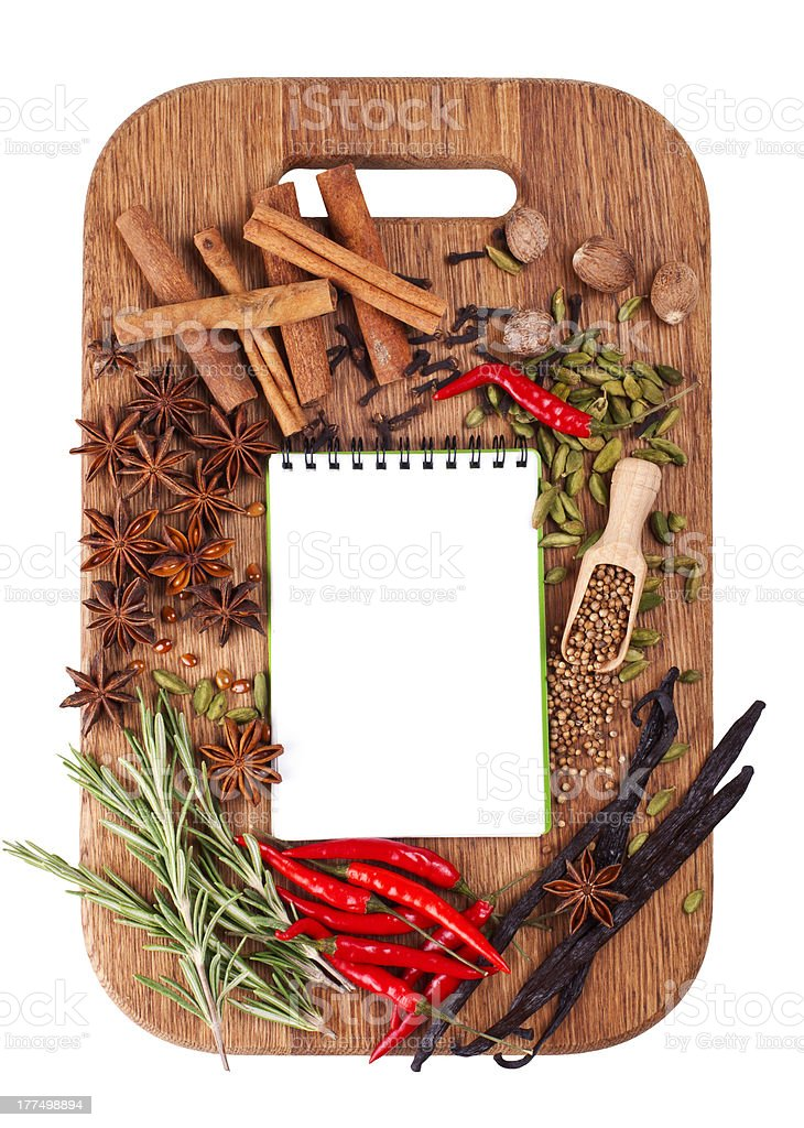 Open notebook with spices and herbs on the cutting board royalty-free stock photo
