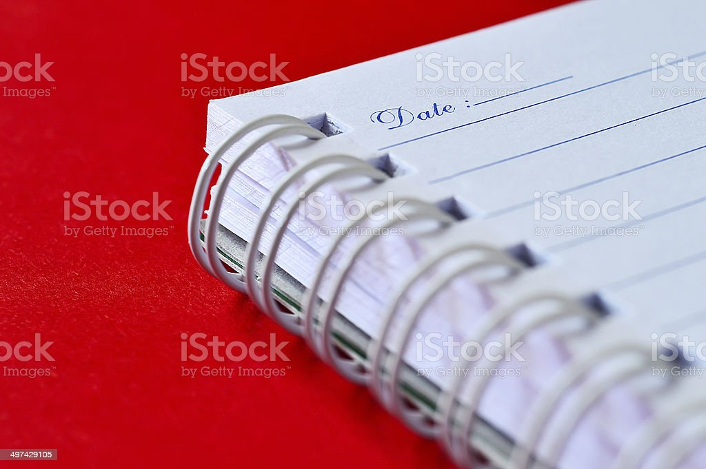 Open notebook with the title page Date in focus isolated stock photo