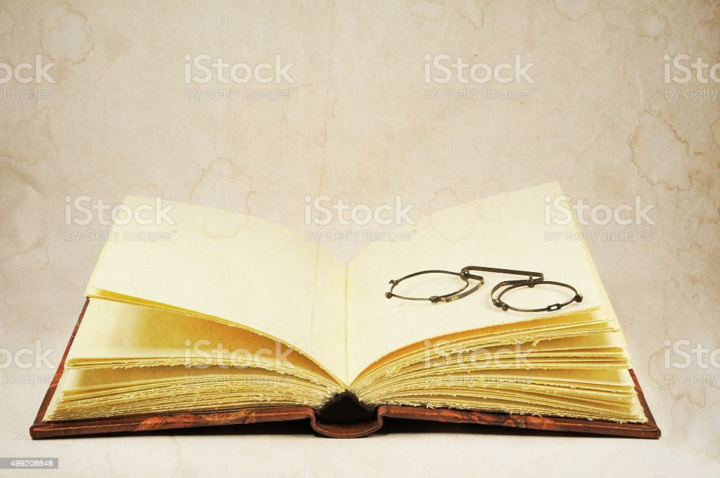 Open old book and pince-nez eyeglasses stock photo