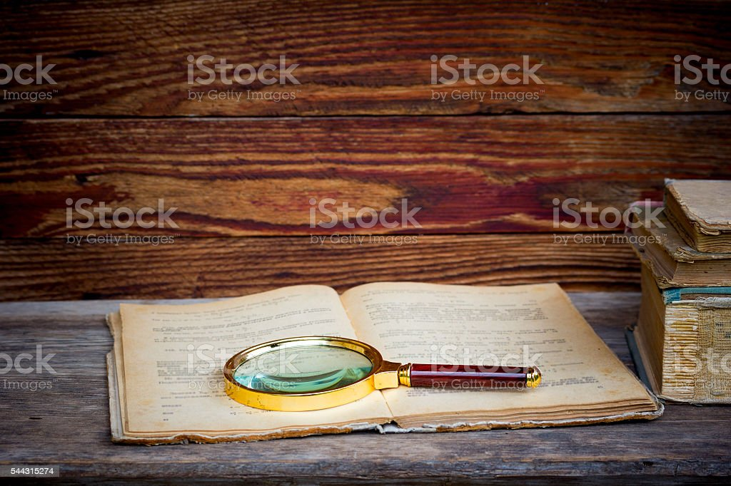open old book with a magnifying glass stock photo