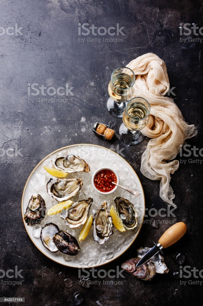 Open Oysters with spicy sauce and champagne stock photo