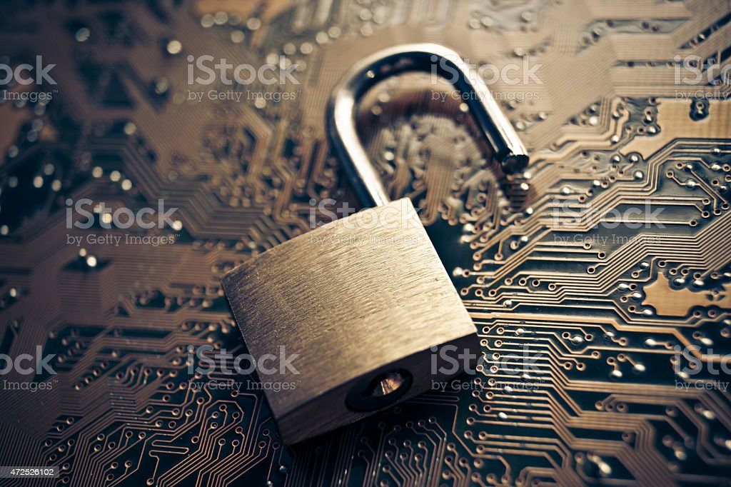 Open padlock on a motherboard signifying security breach stock photo