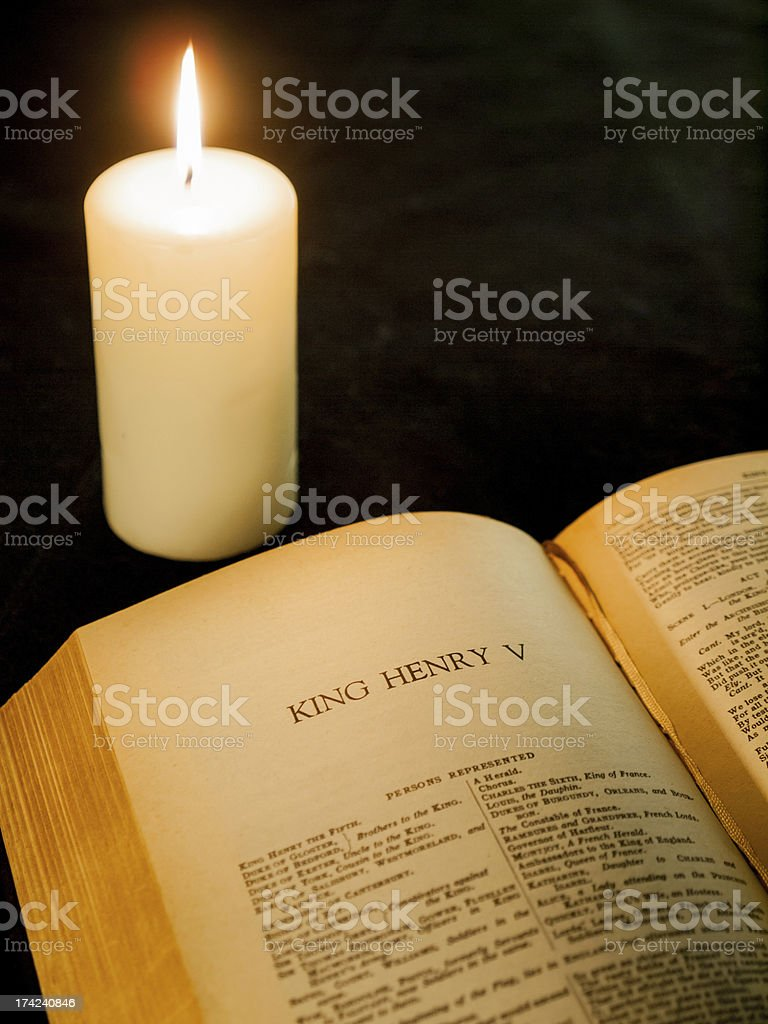 open page the complete works of shakespeare and burning candle stock photo