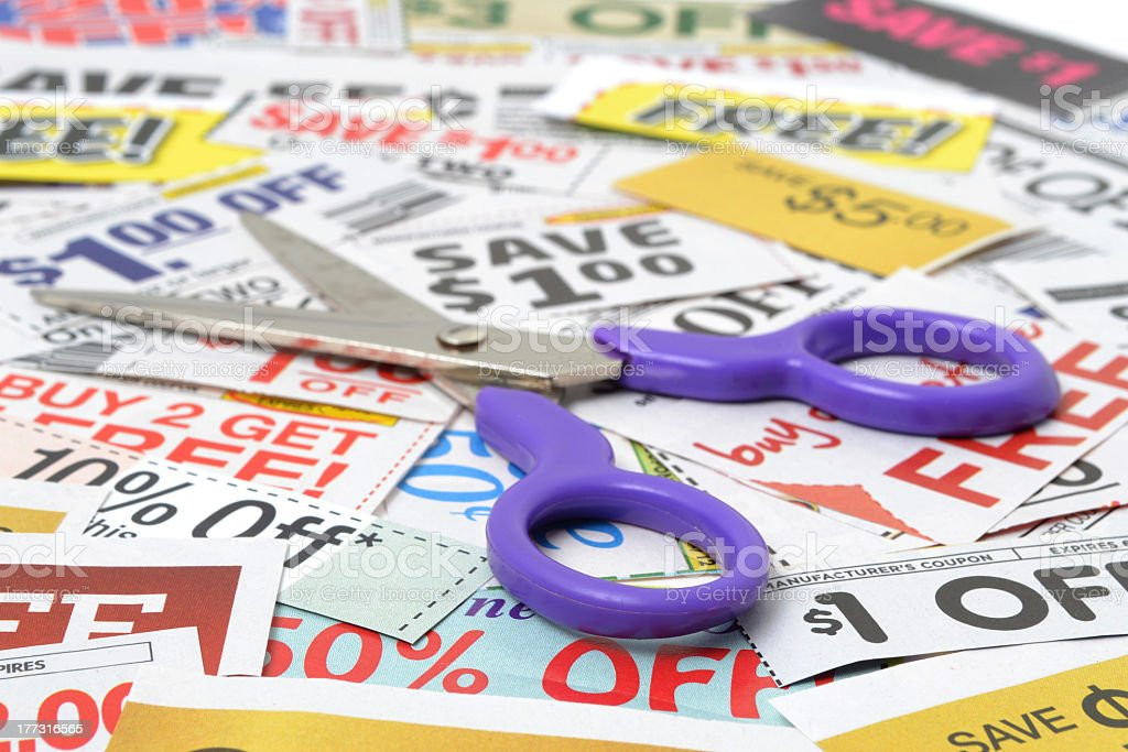 Open pair of scissors on top of a pile of coupons stock photo