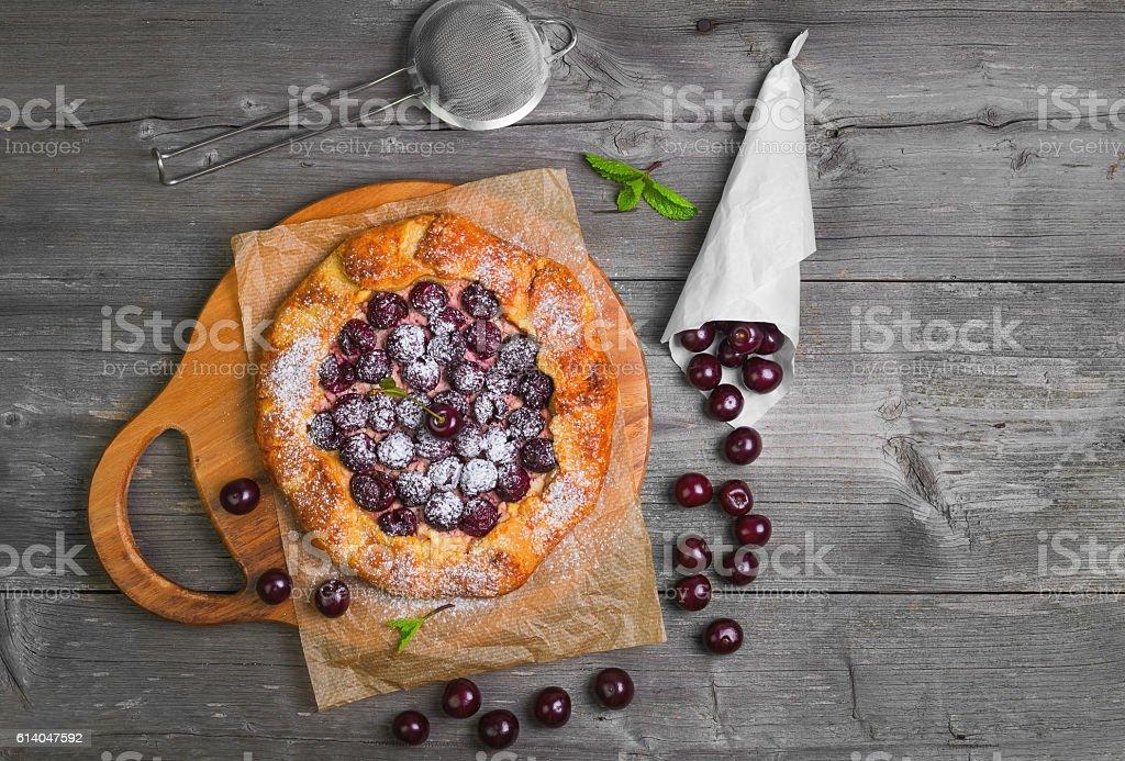 Open pie tart dough with ripe cherries stock photo