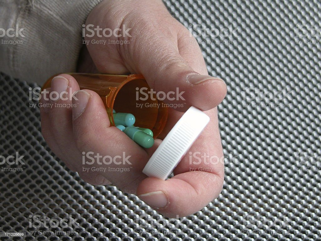 Open pill bottle in hand royalty-free stock photo