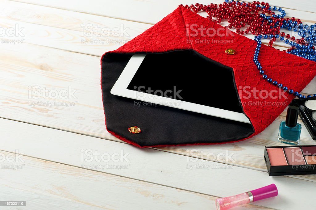 open red ladies bag with tablet in white wooden background stock photo