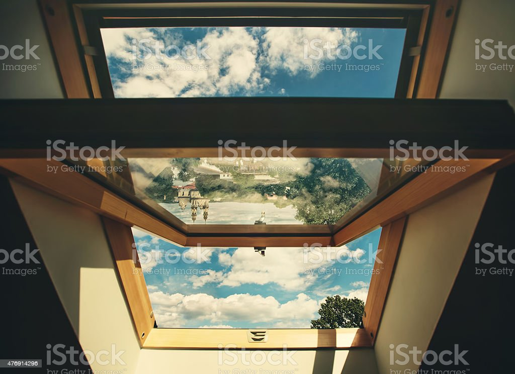 Open roof window skylight with old European city reflection stock photo