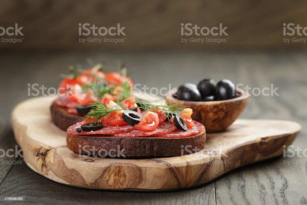 open rye sandwich with salami and vegetables stock photo