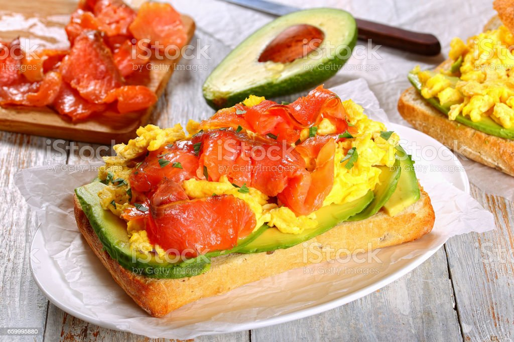 open sandwich with omelette, avocado and salmon stock photo