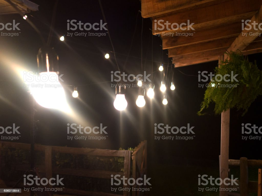 Open String lights hanging in a row against garden stock photo
