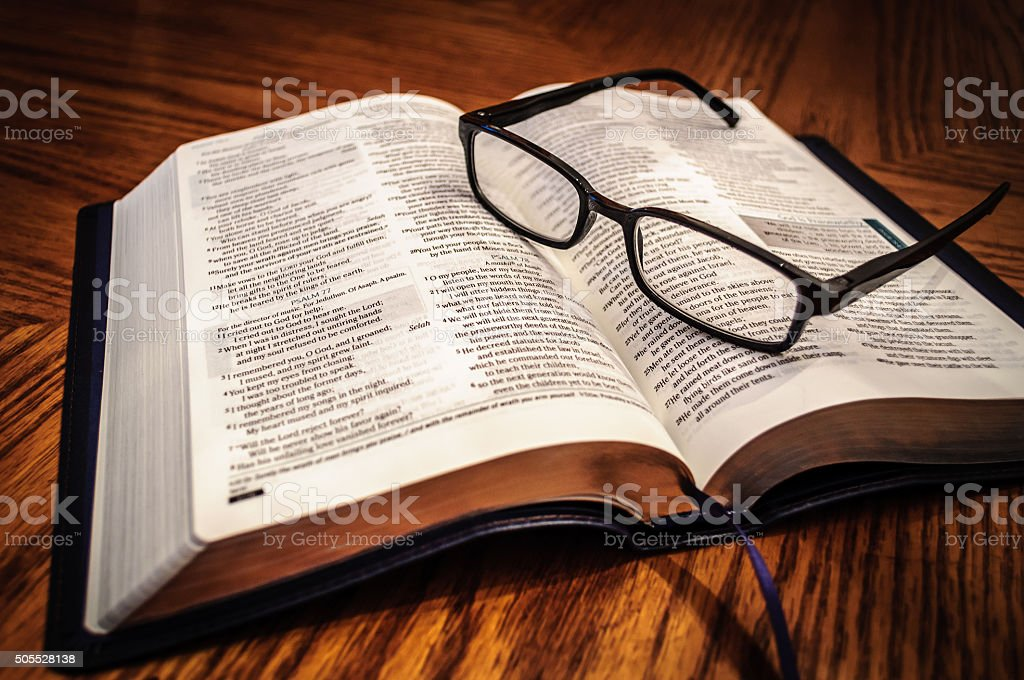 Open Study Bible On Table With Glasses stock photo