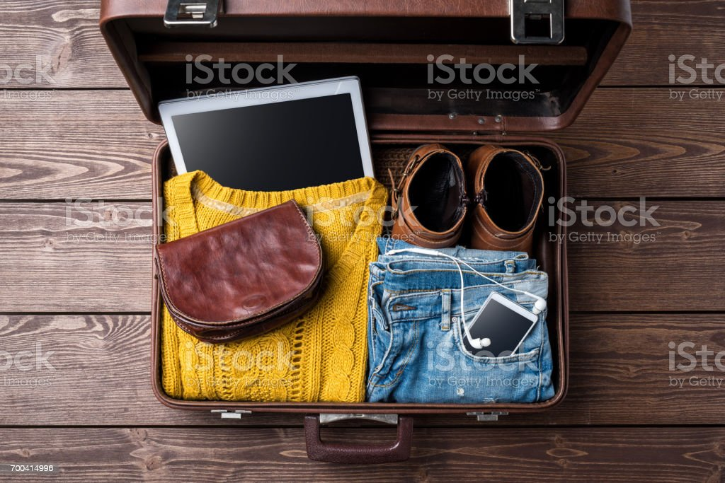 Open suitcase with casual female winter clothes on wooden table. stock photo