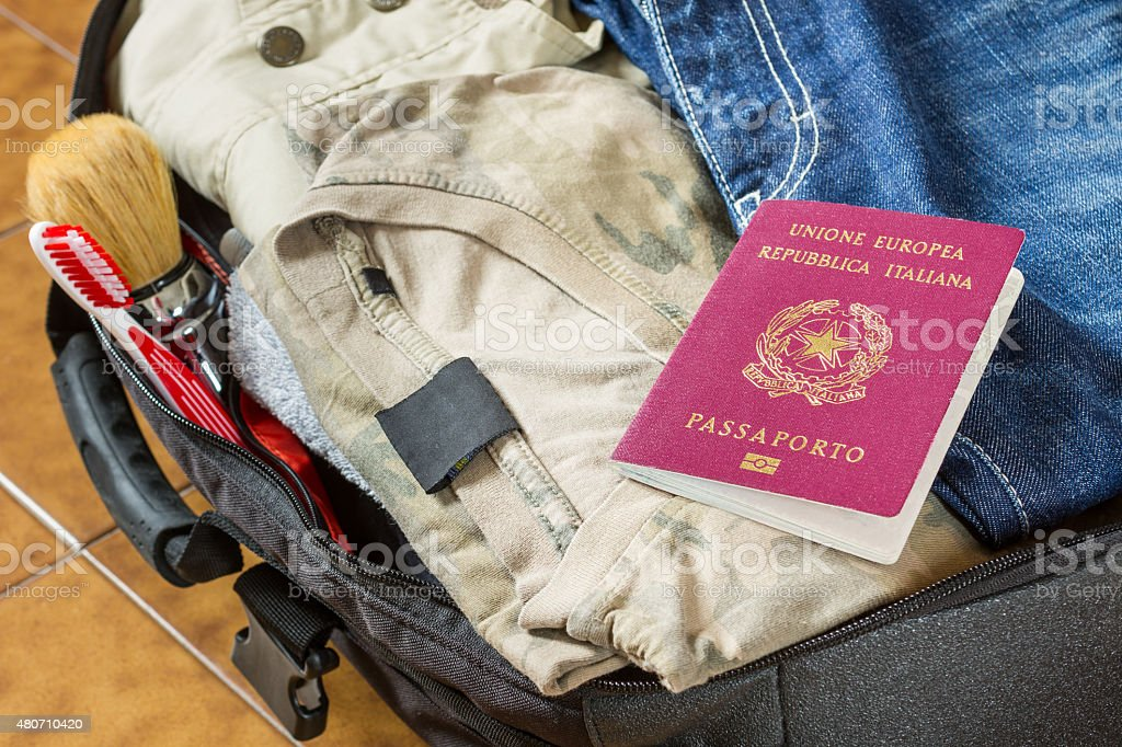 Open suitcase with clothes, personal effects and an italian passport stock photo