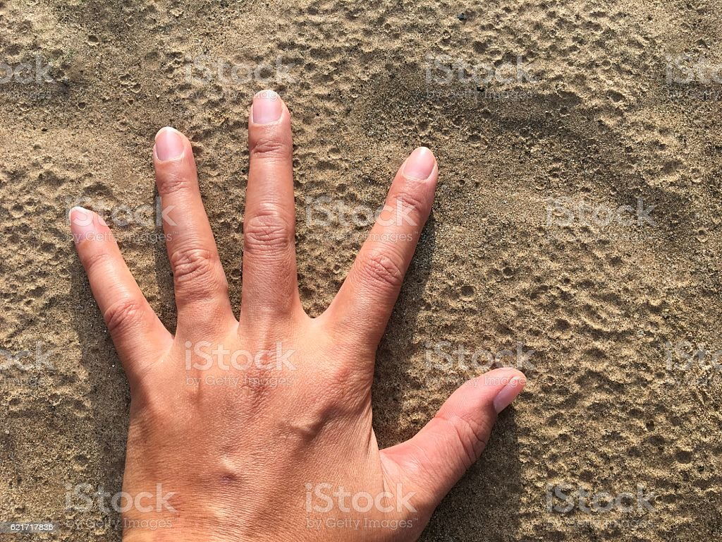 Open the palm of the left hand on the sand, touch royalty-free stock photo