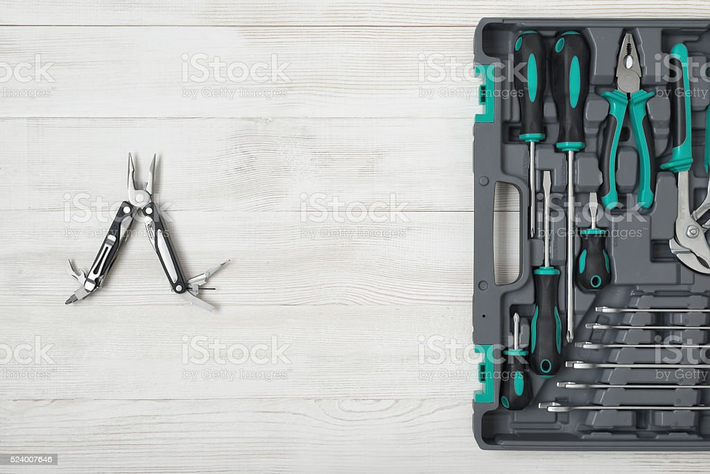 Open toolbox and multi tool on wooden surface stock photo