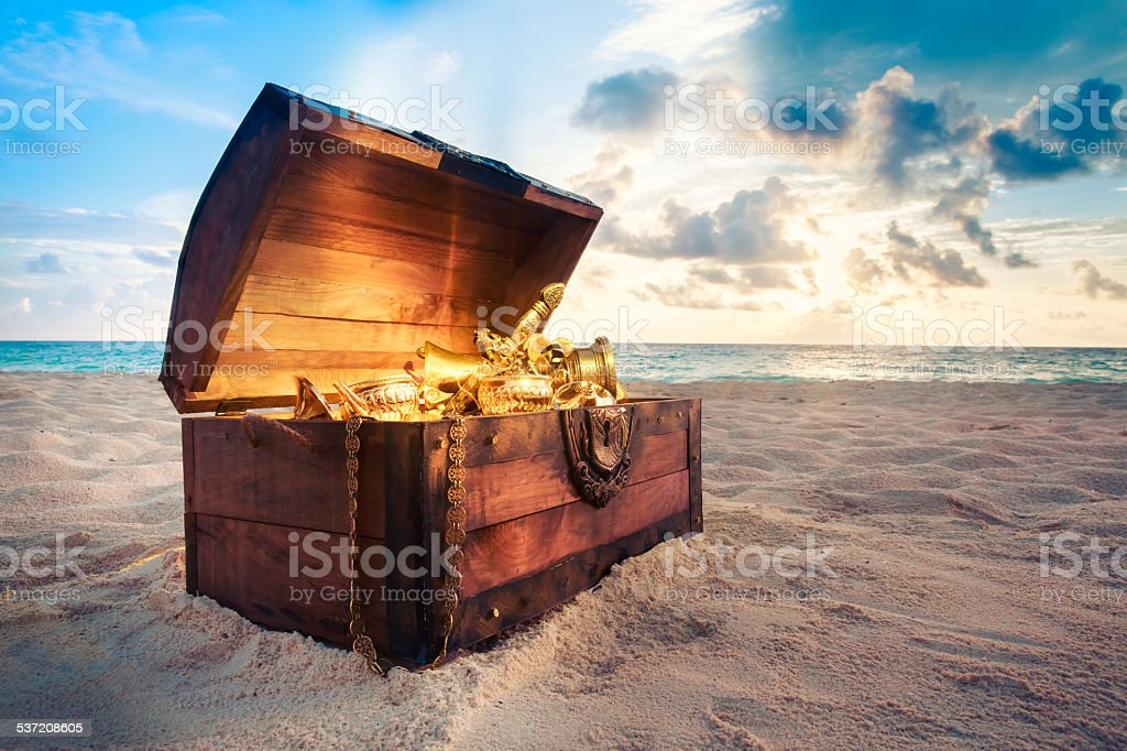 Open treasure chest on the beach stock photo