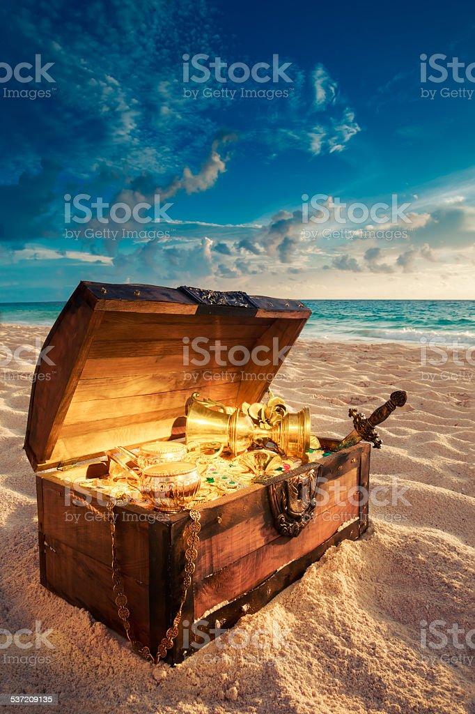 Open treasure chest on the beach stock photo