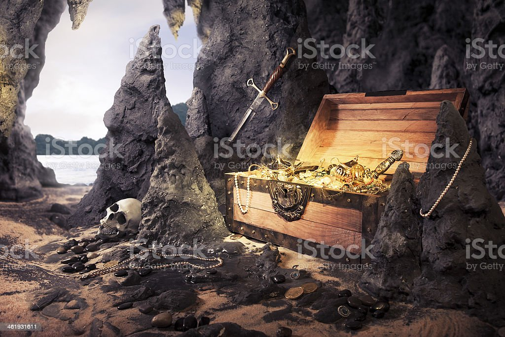 open treasure chest with shinny gold in a cave stock photo